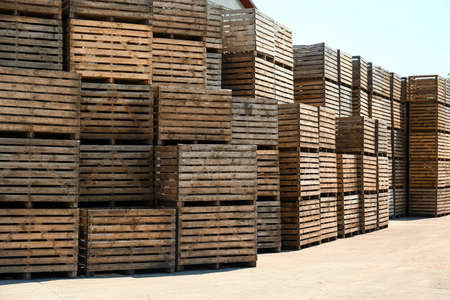 Pile of empty wooden crates outdoors on sunny day. Space for text