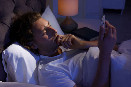 Handsome young man using smartphone in dark room at night. Bedtime