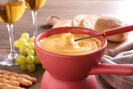 Pot with delicious cheese fondue and bread on table