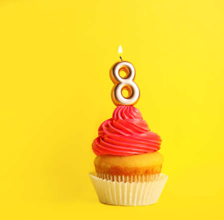 Birthday cupcake with number eight candle on yellow background, space for text