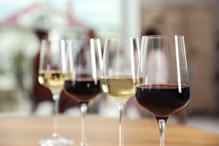 Gläser mit verschiedenen Weinen auf dem Tisch vor unscharfem Hintergrund