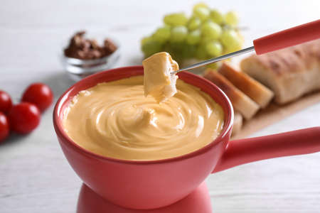 Dipping bread into pot with cheese fondue on table, closeup Stock Photo