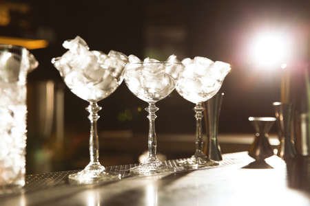 Martini glasses with ice cubes on bar counter. Space for text 写真素材