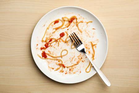 Schmutziger Teller mit Essensresten und Gabel auf Holzuntergrund, Ansicht von oben