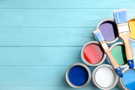Open cans with paint and brushes on blue wooden table, flat lay. Space for text