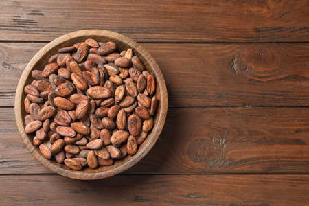 Bowl with cocoa beans on wooden table, top view. Space for text 写真素材 - 129532074
