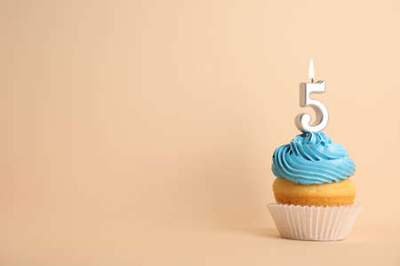 Birthday cupcake with number five candle on beige background, space for text 写真素材 - 129532091