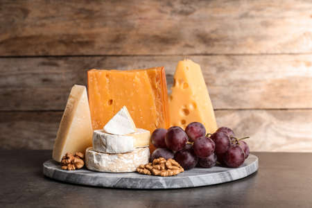 Composition with assorted cheese, grapes and walnuts on table against wooden background 写真素材 - 129532263