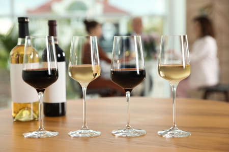 Bottles and glasses with different wines on table against blurred background