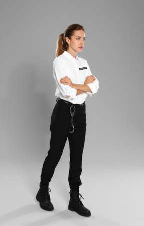 Female security guard in uniform on grey background