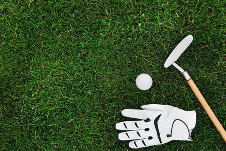 Golf club, ball and glove on green grass, flat lay. Space for text