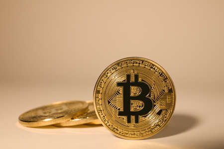 Shiny gold bitcoins on beige background. Digital currency