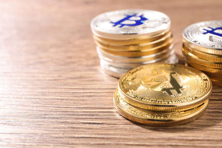 Shiny bitcoins on wooden background, space for text. Digital currency