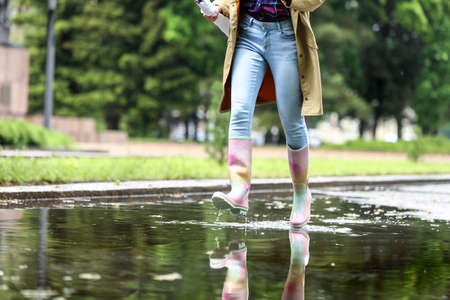 Woman with rubber boots running in puddle, closeup. Rainy weather