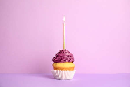 Birthday cupcake with candle on violet background Stock fotó