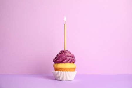 Verjaardag cupcake met kaars op violette achtergrond Stockfoto