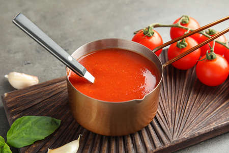 Pan with tomato sauce and spoon on wooden board, closeup Stock Photo