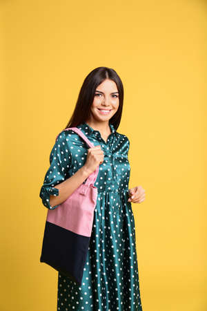 Portrait of young woman with textile bag on yellow background