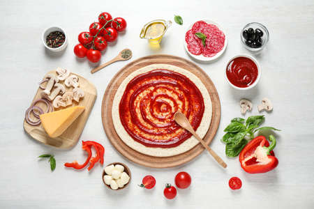 Flat lay composition with pizza crust and ingredients on white wooden table