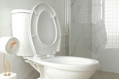 Cuvette de toilette près de la cabine de douche à l'intérieur de la salle de bains moderne Banque d'images