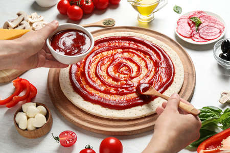Woman spreading tomato sauce onto pizza crust and ingredients on white wooden table, closeup