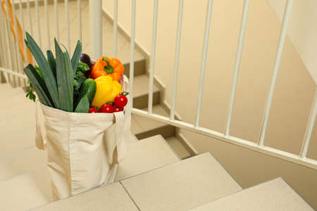 Tote bag with vegetables on stairs indoors. Space for text