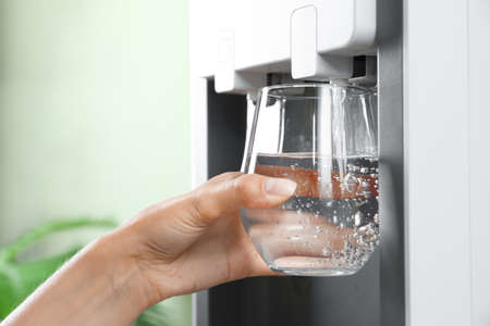 Woman filling glass from water cooler indoors, closeup. Refreshing drink Banco de Imagens
