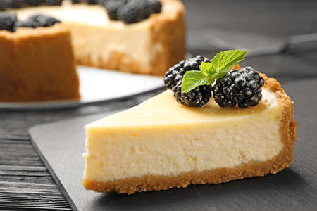Piece of delicious cheesecake decorated with blackberries on table
