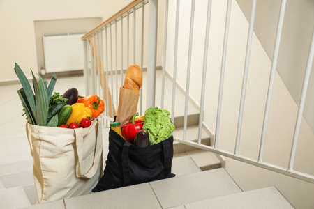 Tote bags with vegetables and other products on stairs indoors. Space for text
