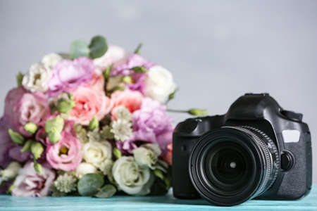 Modern camera and bouquet on light blue wooden table. International Photographers day