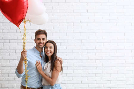 Young couple with air balloons near white brick wall. Celebration of Saint Valentine's Day