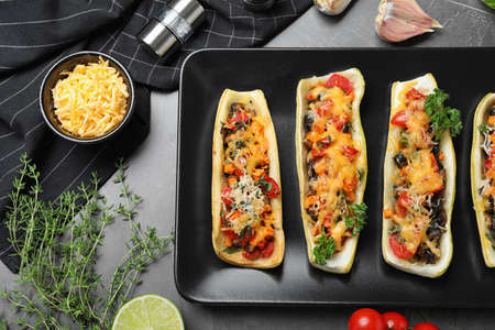 Flat lay composition with delicious stuffed zucchini on grey table 写真素材 - 129531682