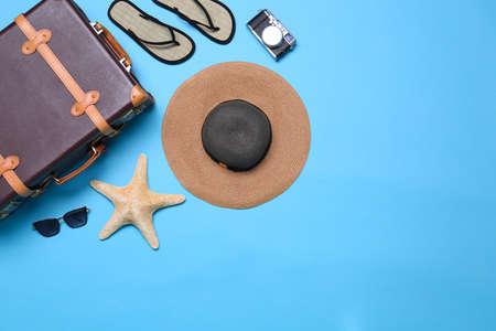 Valigia vintage e oggetti da spiaggia su sfondo blu, distesi. Spazio per il testo