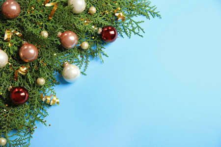 Fir tree branches with Christmas decoration on light blue background, flat lay. Space for text Stockfoto