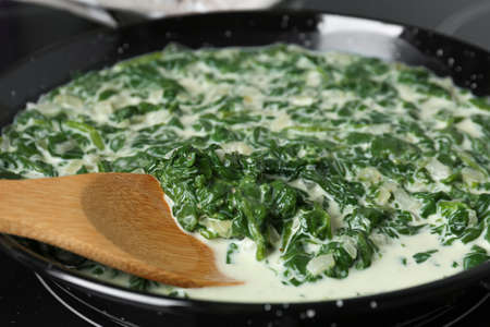 Tasty spinach dip with wooden spoon in frying pan, closeup view 写真素材 - 129531899