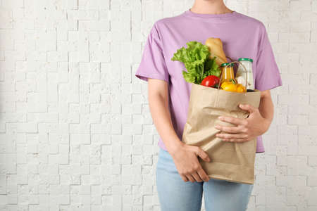 Woman holding shopping paper bag with different groceries against white brick wall. Space for text 写真素材 - 129531901