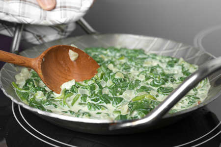 Woman cooking tasty spinach dip on kitchen stove, closeup view 写真素材 - 129532031