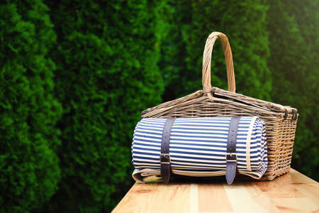 Wicker picnic basket with blanket on wooden table in park. Space for text 스톡 콘텐츠