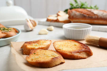 Slices of delicious toasted bread with garlic on table 写真素材 - 129532185