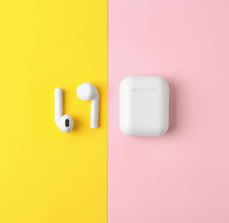 Modern wireless earphones and charging case on color background, flat lay