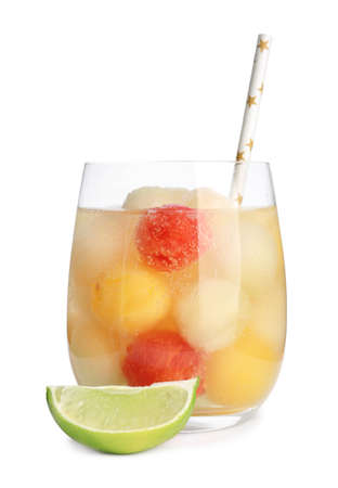 Glass of melon and watermelon ball cocktail with lime on white background