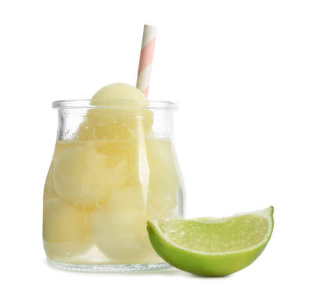 Glass jar of melon ball cocktail and lime on white background