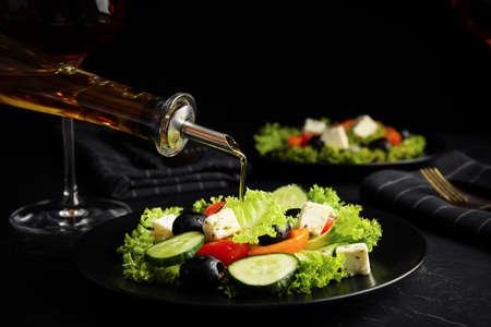 Dressing tasty fresh Greek salad with olive oil on dark table Stok Fotoğraf