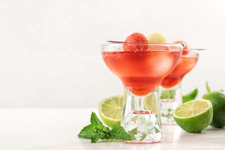 Glass of melon and watermelon ball cocktail on white wooden table. Space for text 写真素材