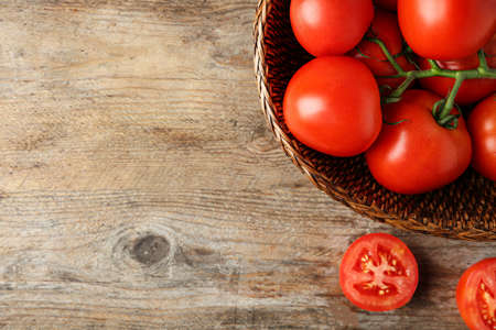 Fresh ripe red tomatoes in wicker bowl on wooden table, top view. Space for text