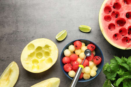Flat lay composition with melon and watermelon balls on grey background
