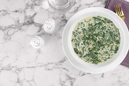 Gustosa salsa di spinaci su un tavolo di marmo bianco, distesa piatta