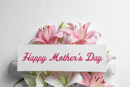 Beautiful lily flowers and card with text Happy Mothers Day on white background, top view