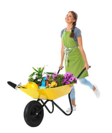 Female gardener with wheelbarrow and plants on white background