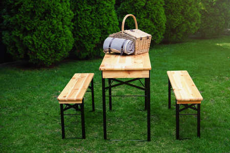 Wicker picnic basket with blanket on wooden table in park